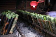 Sukri pours coconut milk into a line of bamboo tubes. JP/P.J. Leo