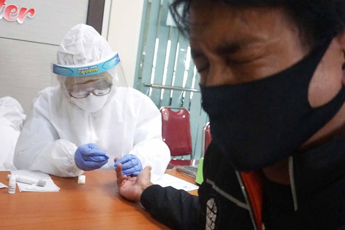 A man closes his eyes as an officer takes his blood sample at the Malang City Health Office in East Java on May 18. The city administration aims to provide rapid tests for those who face a high risk of contracting COVID-19. JP/Nedi Putra A.W.