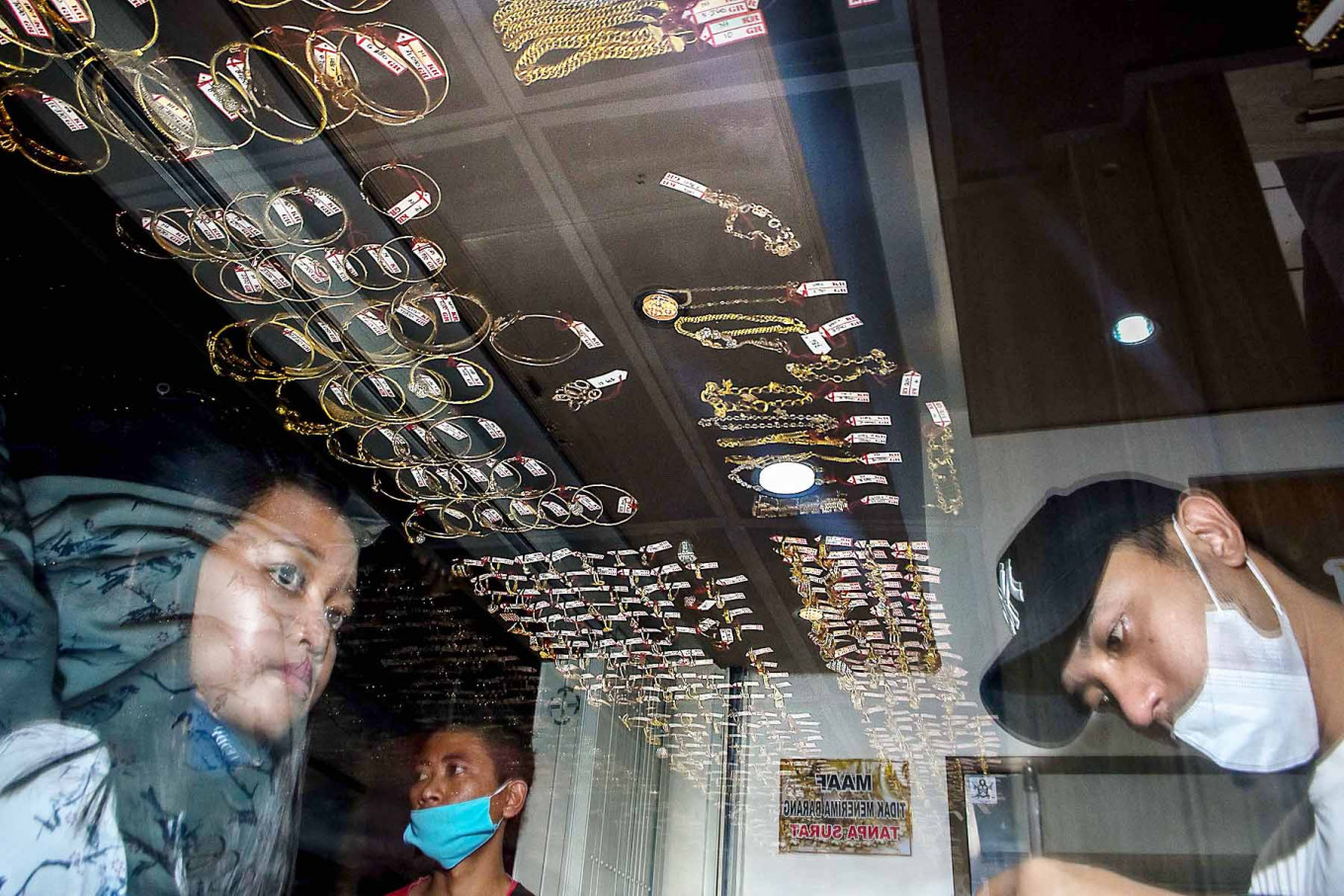 Two consumers (left) complete their transactions at a gold shop in Singosari Market in Malang, East Java, on May 19. The store recorded a surge of gold jewelry sales ahead of Idul Fitri, rising from 10 to 25 transactions per day. JP/Aman Rochman