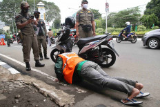 A Public Order Agency (Satpol PP) officer takes a picture of a motorist who does pushups as a punishment for violating the large-scale social restrictions (PSBB) in Depok, West Java, on May 19. Punishments for offenders of the PSBB range from pushups and singing the national anthem to sweeping the streets. JP/P.J. Leo