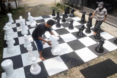 Two men play giant chess in front of a house in Pondok Betung in South Tangerang, Banten, on May 15 while waiting to break the fast. JP/Wendra Ajistyatama