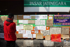 A visitor looks at a merchant information board on May 15 at East Jakarta's Jatinegara Market, which is temporarily closed due to the city's large-scale social restrictions. The board contains the phone numbers of market merchants who have continued to offer their services. JP/Dhoni Setiawan