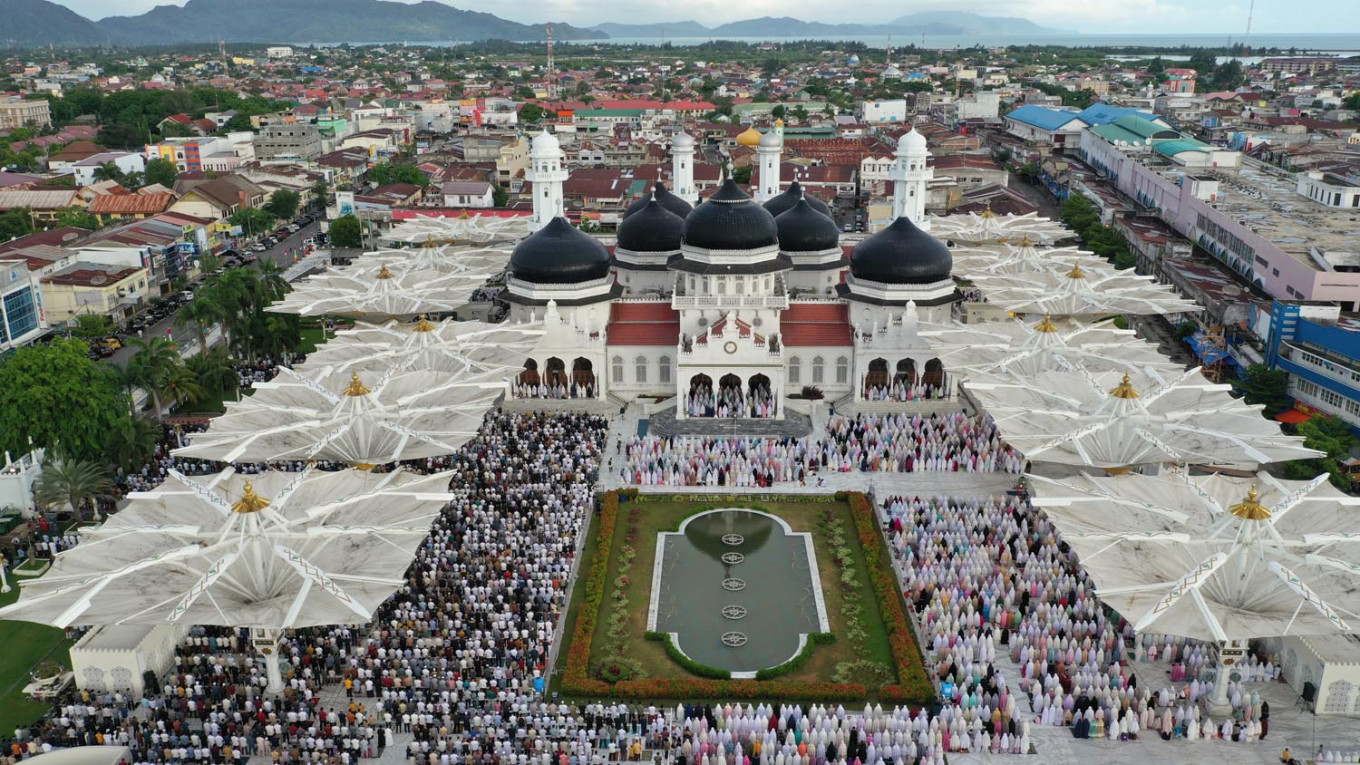 Business as usual: An aerial photograph shows people attending Idul Fitri prayers, marking the end of Ramadan at Baiturrahman Mosque in Banda Aceh, Aceh province, on Sunday. AFP/Adi Gondronk