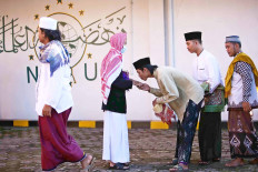 Giving thanks: A young man shows his respect to an older community member during an Idul Fitri celebration at the Jami' Al-Makmur mosque in Leuwinanggung, Depok, West Java, on Sunday. JP/P.J.  Leo)