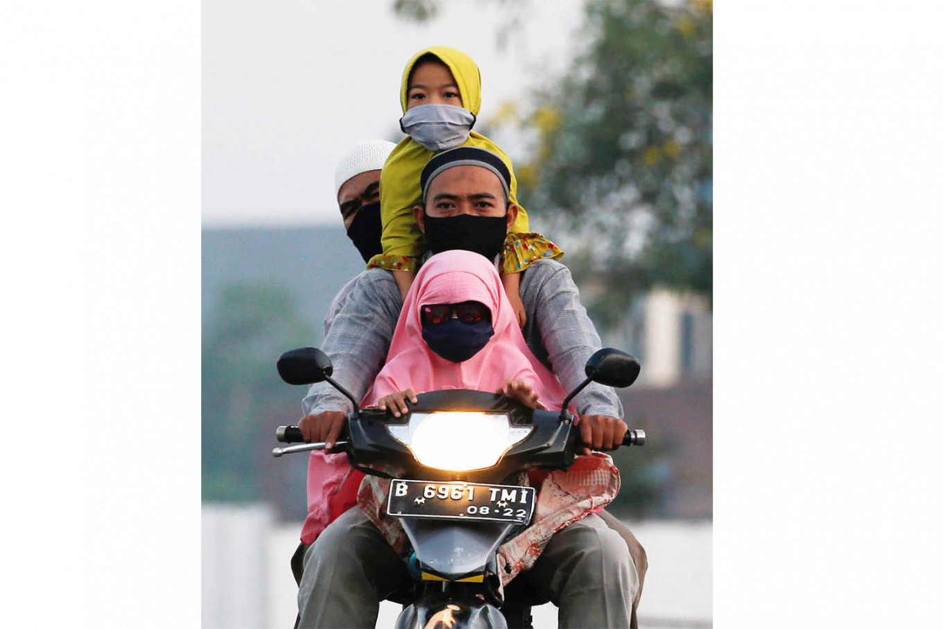 Family bonding: Two men and a young girl ride a motorcycle to attend Idul Fitri prayers amid the COVID-19 outbreak in Bekasi, West Java, on Sunday. Reuters/Willy Kurniawan