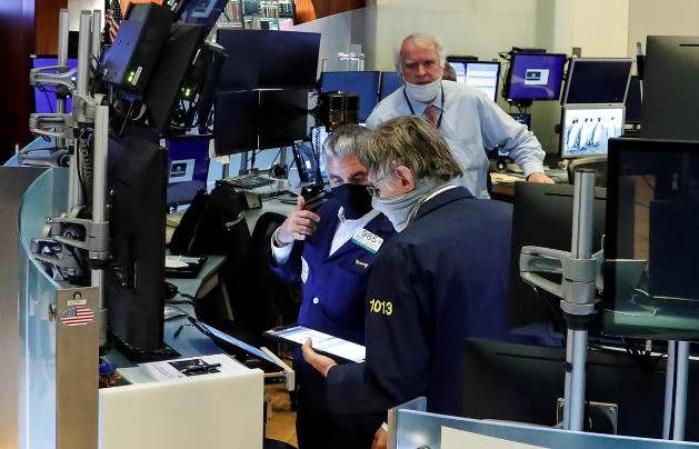 Traders wearing masks work on the first day of in person trading since the closure during the outbreak of the COVID-19 on the floor at the New York Stock Exchange in New York United States