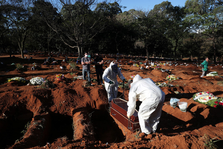 Gravediggers wearing protective suits prepare to bury the coffin of Izolina de Sousa, 85, who died from the coronavirus disease (COVID-19), at Vila Formosa cemetery, Brazil's biggest cemetery, in Sao Paulo, Brazil, May 26, 2020.