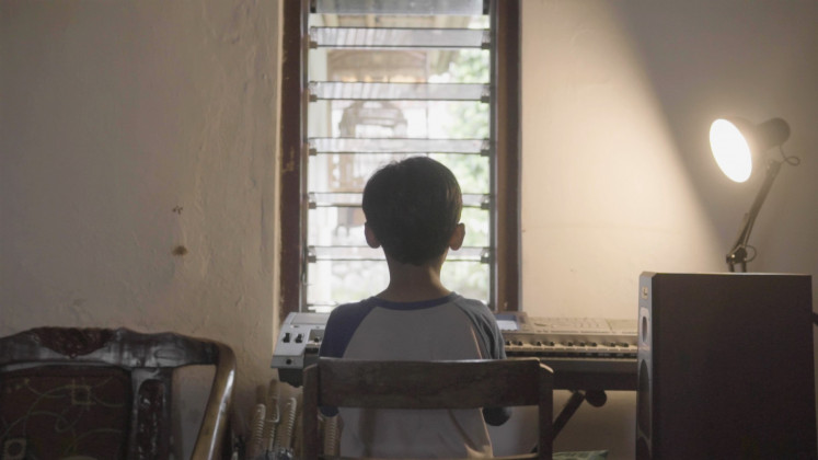 Creative endeavors: Many people turn to playing music and reading books to cope with the lockdown as captured in scenes from the short film 'Cerita tentang Jendela' (Stories About Windows).