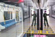 "Soldiers stand guard at the MRT station in the Hotel Indonesia traffic circle in Jakarta on Tuesday, May 26. President Joko Widodo deploys military personnel to guard the implementation of the ""new normal"" protocols in the capital. JP/Seto Wardhana."