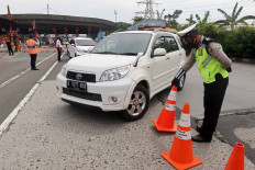 A police officer orders a car's driver to make a U-turn at the Cikupa toll gate in Tangerang, Banten, on Wednesday May 27, to prevent the car from entering Jakarta. The police only grant access to travelers who have Jakarta Exit and Entry Permit (SIKM). JP/Dhoni Setiawan