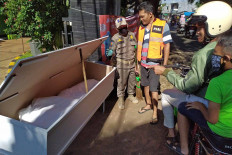 A Jakarta Public Order Agency (Satpol PP) officer shows a mockup coffin and corpse to a man in an orange vest, who violated the social distancing policy, at the entrance of Pondok Ranggon public cemetery in East Jakarta on May 25. JP/P.J.Leo