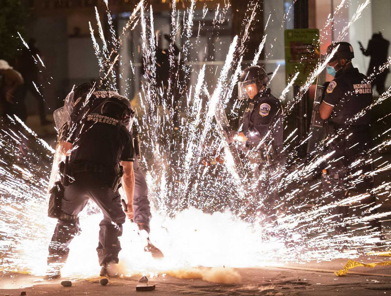 """A firecracker thrown by protesters explodes under police one block from the White House on May 30, 2020 in Washington DC, during a protest over the death of George Floyd, an unarmed black man, who died after a Minneapolis  police officer kneeled on his neck for several minutes. - Clashes broke out and major cities imposed curfews as America began another night of unrest Saturday with angry demonstrators ignoring warnings from President Donald Trump that his government would stop violent protests over police brutality """"cold."""" AFP/Andrew-Caballero Reynolds"""