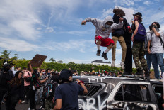 """Demonstrators jump on a damaged police vehicle in Los Angeles on May 30, 2020 during a protest against the death of George Floyd, an unarmed black man who died while while being arrested and pinned to the ground by the knee of a Minneapolis police officer. - Clashes broke out and major cities imposed curfews as America began another night of unrest Saturday with angry demonstrators ignoring warnings from President Donald Trump that his government would stop violent protests over police brutality """"cold."""" AFP/Ariana Drehsler"""