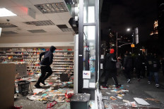 """People loot a store during demonstrations over the death of George Floyd by a Minneapolis police officer on June 1, 2020 in New York. - New York's mayor Bill de Blasio today declared a city curfew from 11:00 pm to 5:00 am, as sometimes violent anti-racism protests roil communities nationwide. Saying that """"we support peaceful protest,"""" De Blasio tweeted he had made the decision in consultation with the state's governor Andrew Cuomo, following the lead of many large US cities that instituted curfews in a bid to clamp down on violence and looting. AFP/Bryan R. Smith"""