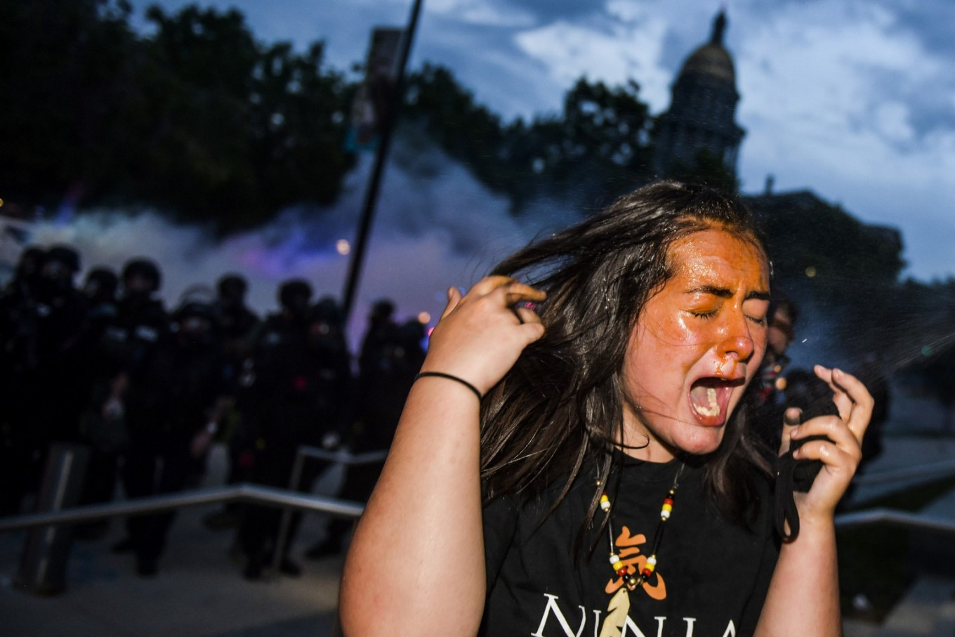 A woman reacts after being sprayed by pepper spray next to the Colorado State Capitol as protests against the death of George Floyd continue for a third night on May 30, 2020 in Denver, Colorado. The city of Denver enacted a curfew for Saturday and Sunday nights and Governor Jared Polis activated the Colorado National Guard in hopes of stopping protests that have wreaked havoc across the city.   AFP/ Getty Images/ Michael Ciaglo
