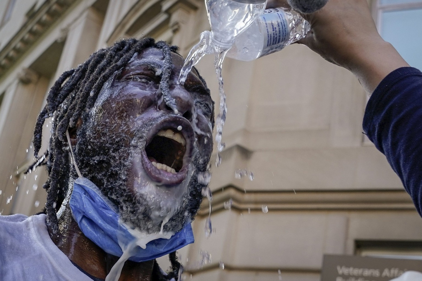 A demonstrator is doused with water and milk after being hit with pepper spray from law enforcement during a protest on June 1, 2020 in downtown Washington, DC. Protests and riots continue in cities across America following the death of George Floyd, who died after being restrained by Minneapolis police officer Derek Chauvin. Chauvin, 44, was charged last Friday with third-degree murder and second-degree manslaughter. AFP/Getty Images/Drew Angerer