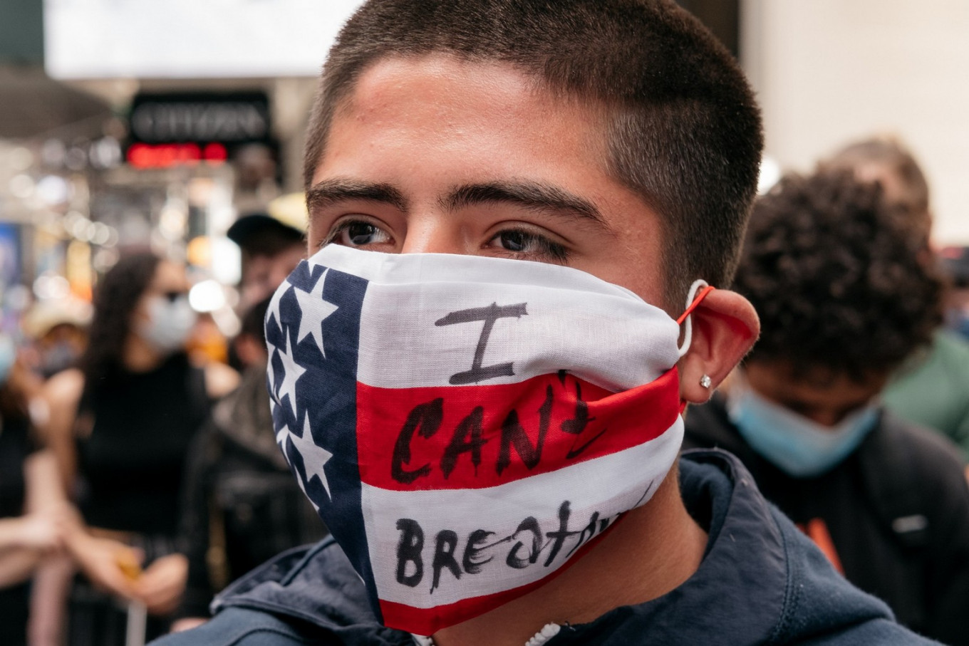 """A young man wears a mask that reads """"I Can't Breathe"""" during a rally in Times Square denouncing racism in law enforcement and the May 25 killing of George Floyd while in the custody of Minneapolis, on June 1, 2020 in New York City. Days of protest, sometimes violent, have followed in many cities across the country.   AFP/Getty Images/Scott Heins"""