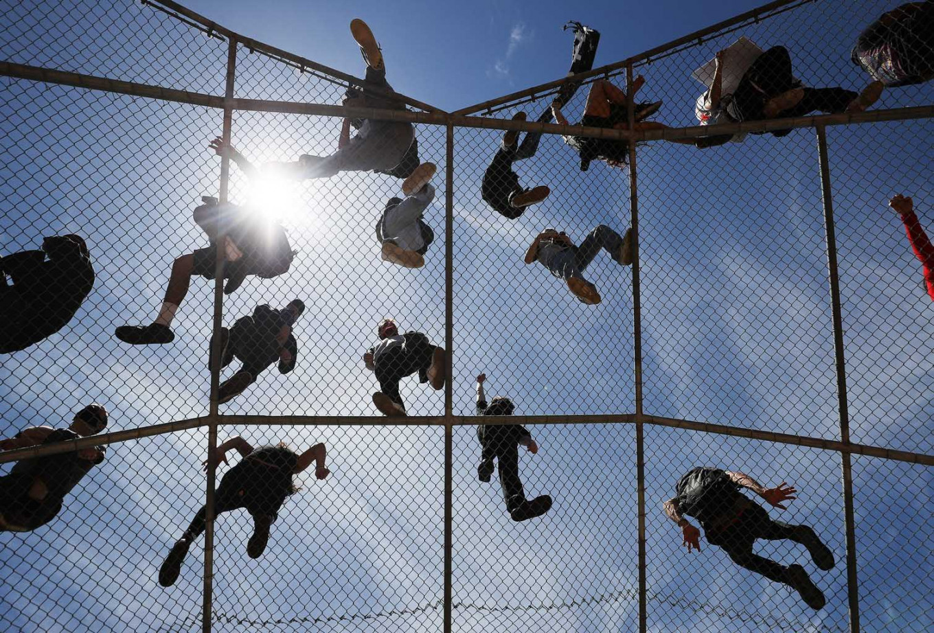 Protestors listen to speeches from atop a baseball backstop during a Black Lives Matter demonstration following the death of George Floyd on May 30, 2020 in Los Angeles, California. The vast majority of protestors demonstrated peacefully. Former Minneapolis police officer Derek Chauvin was taken into custody for Floyd's death. Chauvin has been accused of kneeling on Floyd's neck as he pleaded with him about not being able to breathe. Floyd was pronounced dead a short while later. Chauvin and 3 other officers, who were involved in the arrest, were fired from the police department after a video of the arrest was circulated. AFP/Getty Images/Mario Tama
