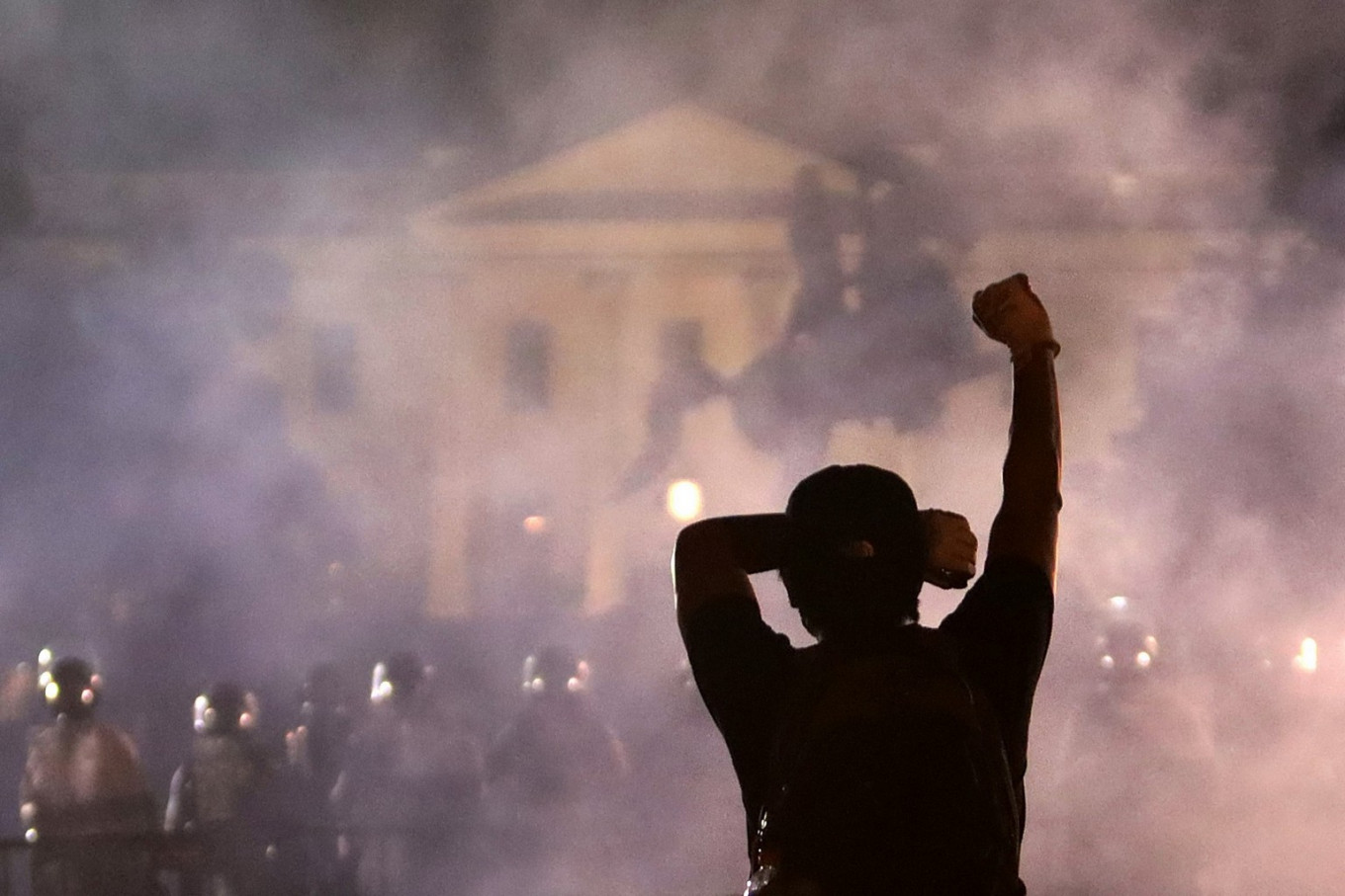 A man holds up his fist during a protest near the White House on May 31, 2020 in Washington, DC. Minneapolis police officer Derek Chauvin was arrested for Floyd's death and is accused of kneeling on Floyd's neck as he pleaded with him about not being able to breathe. Floyd was pronounced dead a short while later. Chauvin and three other officers, who were involved in the arrest. AFP/Getty Images/Alex Wong