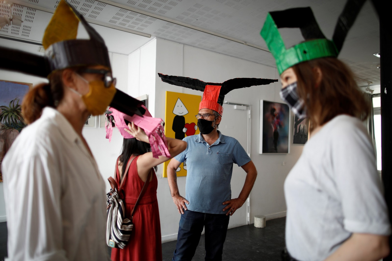 Winging it: Paris gallery keeps visitors apart with extension hats