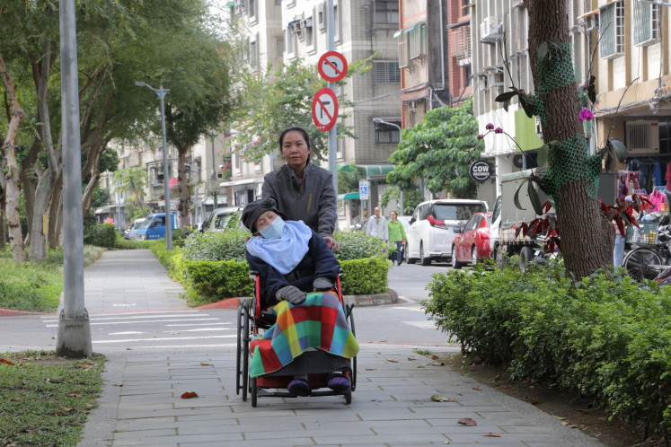 Leisurely stroll: Muji, who has adjusted well to her life in Taiwan, takes her employer's child out for a stroll. She is one of four women who feature in 'Help is on theWay', a documentary that takes a close and intimate look at their lives in Taiwan as domestic workers.