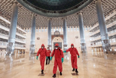 Fire and Rescue Agency personnel wear bright red hazmat suits as they disinfect Istiqlal Mosque in Central Jakarta on Wednesday, in preparation for gradually transitioning the capital out of the large-scale social restrictions (PSBB) over the month of June. JP/Donny Fernando