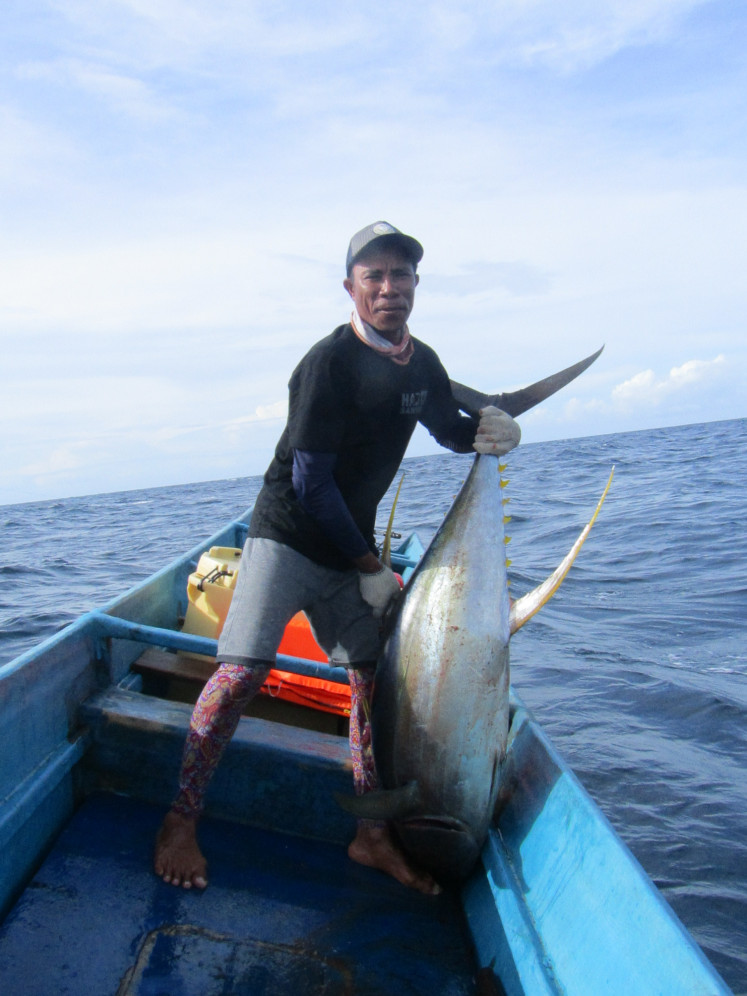 A fisherman from Waprea village, Buru regency, Maluku, Yusran Tomia, shows off his catch, a large yellowfin tuna. Fishermen from Buru Island have set an example for other small-scale fisheries in Indonesia and around the world that sustainable fishing can improve the livelihoods of fishing communities as the global community celebrates World Oceans Day on June 8.