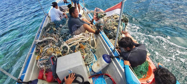 Bawah Reserve staff pull fishing nets out of the water during an ocean cleanup.
