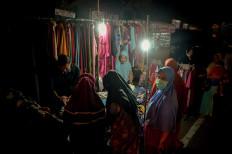 Women gather at a clothing kiosk on the sidewalk of a Pariaman street. JP/Arif Rahman AS