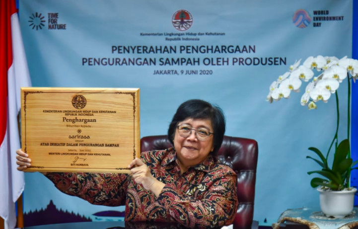 Environment and Forestry Minister Siti Nurbaya Bakar holds up a placard given to companies that have shown progress in reducing the amount of plastic they use and produce during a virtual awarding ceremony in Jakarta on Tuesday.