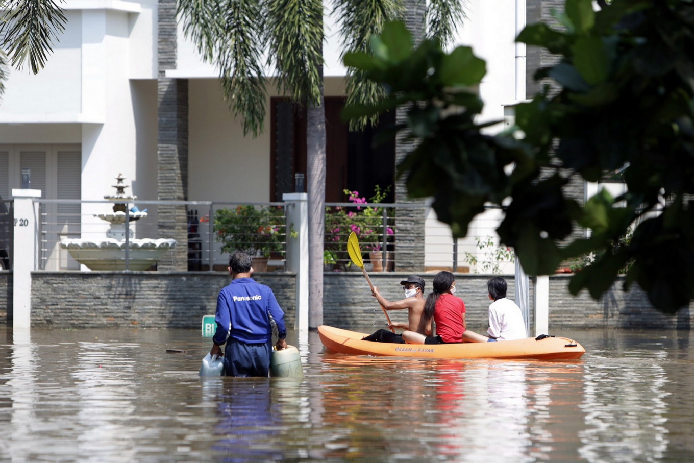 People ride a kayak around the Pantai Mutiara housing complex in North Jakarta on June 7 after a flood hit the area. The flooding began on Friday after a levee was breached, allowing sea water to inundate the area. JP/Wendra Ajistyatama