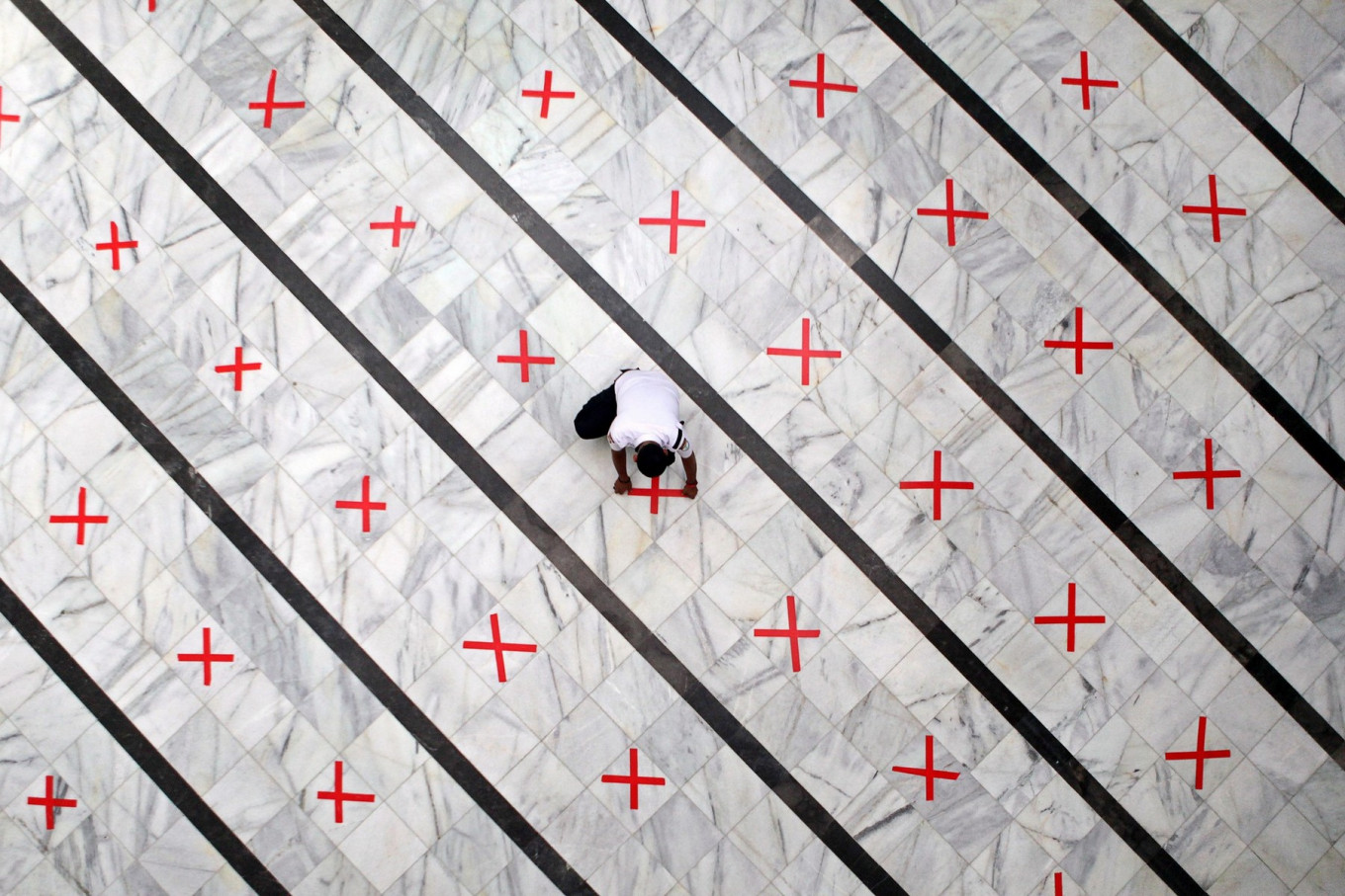 A mosque staff member fixes a physical distancing mark on the floor of the Cut Meutia Mosque in Central Jakarta on Thursday, which had been closed to curb the spread of COVID-19. The city administration has extended large-scale social restrictions but will gradually lift some of the rules, such as allowing houses of worship, shopping centers and offices to open. JP/Seto Wardhana