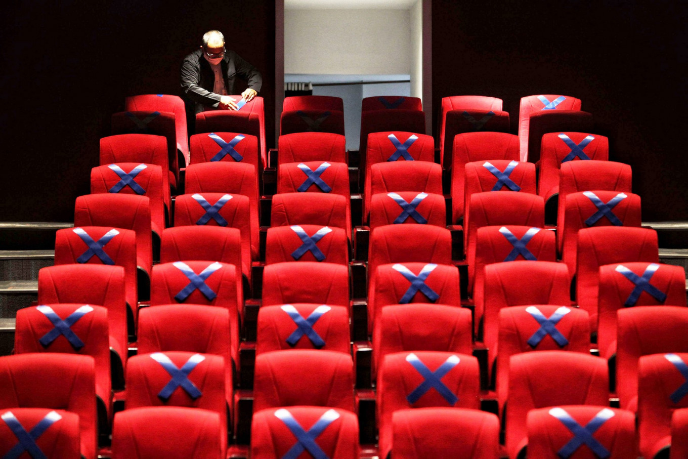A staff member fixes a physical distancing mark on the seats at the auditorium of the National Library in Jakarta on June 9. JP/Seto Wardhana