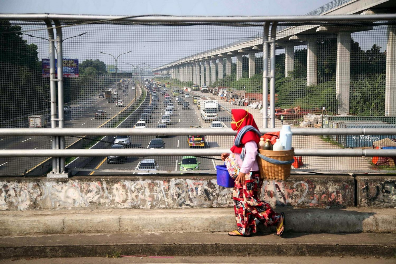 A jamu (herbal medicine) seller crosses a bridge above the Jagorawi toll road in Cibubur, East Jakarta, on Monday. JP/P.J. Leo