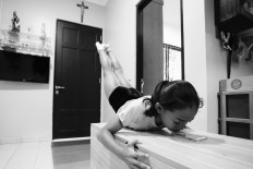 Ave balances on a living room table while throwing her feet up in the air. JP/Toto Santiko Budi