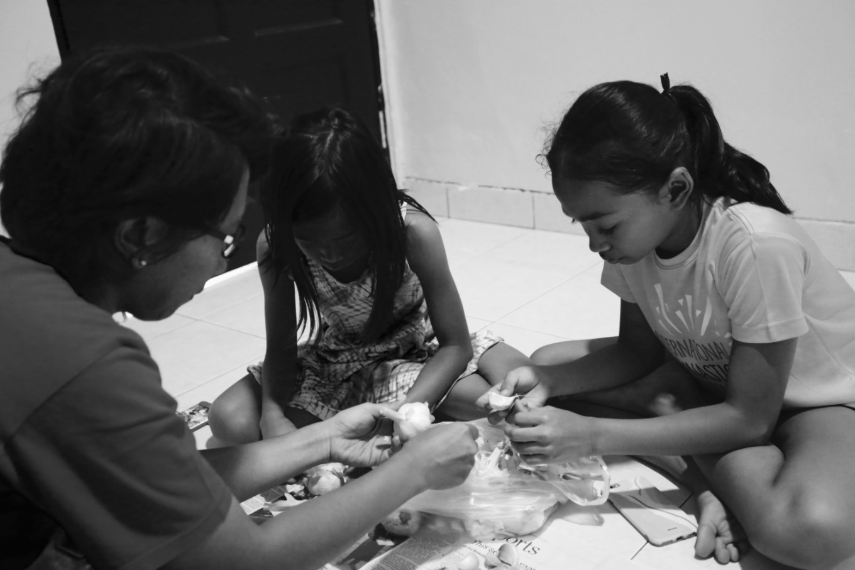 After training, Ave and Agda help their mother, Eta, peel garlic. JP/Toto Santiko Budi
