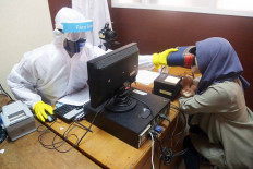 A civil registration officer in full PPE takes an optical scan of a woman on Tuesday to gather biometric data for issuing an electronic identity card at the Population and Civil Registration office in Pondok Aren, South Tangerang, Banten. JP/Wendra Ajistyatama