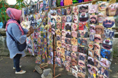 A face mask vendor arranges her display rack on Wednesday near the Bogor regency office in Pakansari, Bogor, West Java. The printed masks, which bear a variety of designs from soccer club logos to pictures of mustached mouths, and even the mouth of Stephen King's Pennywise the Clown, cost from Rp 5,000 (35 US cents) to Rp 15,000 each. JP/P.J. Leo