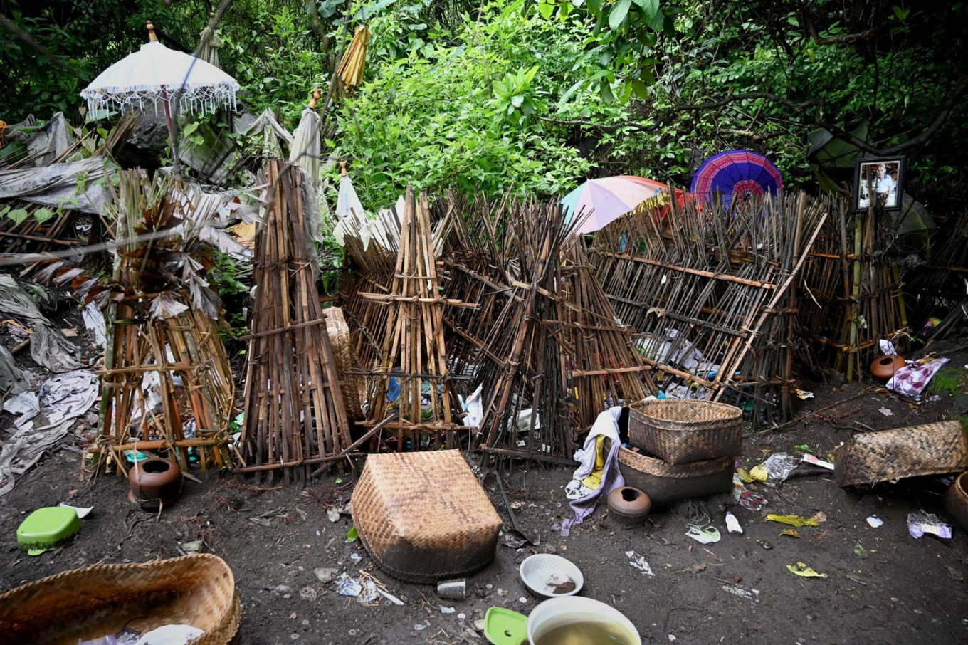 This picture taken on February 20, 2020 shows items (bottom) left from ceremonial offerings for use in the afterlife scattered on the ground next to bamboo cages which cover bodies at a cemetery where Bali's Trunyanese people hold open-air burials - before restrictions were implemented due to the COVID-19 coronavirus - near the village of Trunyan in Bangli Regency, near Lake Batur on Bali island. - For centuries Bali's Trunyanese people have left their dead to decompose in the open air, the bodies placed in bamboo cages until only the skeletons remain -- a ritual they haven't given up -- even as the COVID-19 pandemic upends burial practices worldwide.  AFP/Sonny Tumbelaka