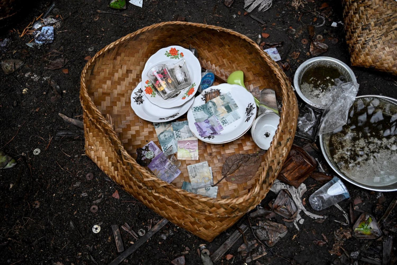 This picture taken on February 20, 2020 shows items left from ceremonial offerings for use in the afterlife scattered on the ground at a cemetery where Bali's Trunyanese people hold open-air burials - before restrictions were implemented due to the COVID-19 coronavirus - near the village of Trunyan in Bangli Regency, near Lake Batur on Bali island. - For centuries Bali's Trunyanese people have left their dead to decompose in the open air, the bodies placed in bamboo cages until only the skeletons remain -- a ritual they haven't given up -- even as the COVID-19 pandemic upends burial practices worldwide. AFP/Sonny Tumbelaka