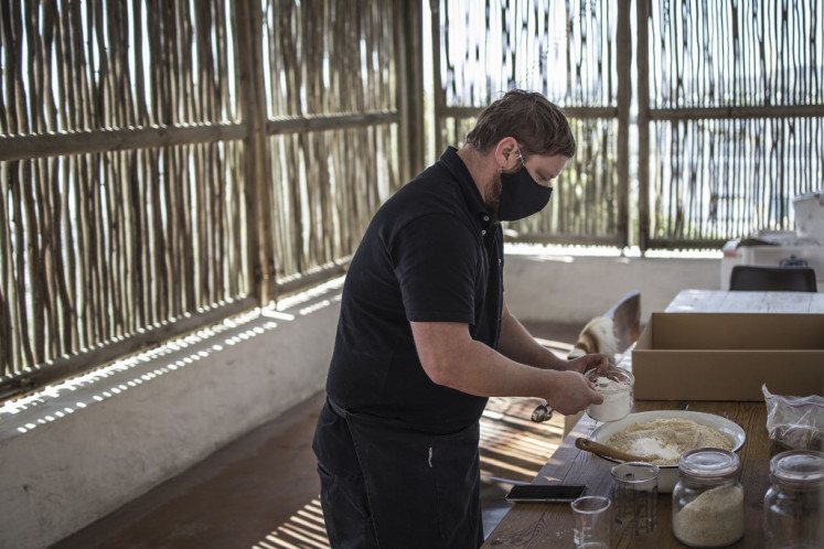 South African Chef Kobus van der Merwe of the Wolfgat restaurant on the beach in Paternoster, South Africa, on June 18, 2020 prepares dry ingredients to be delivered to customers for a at-home bake.
