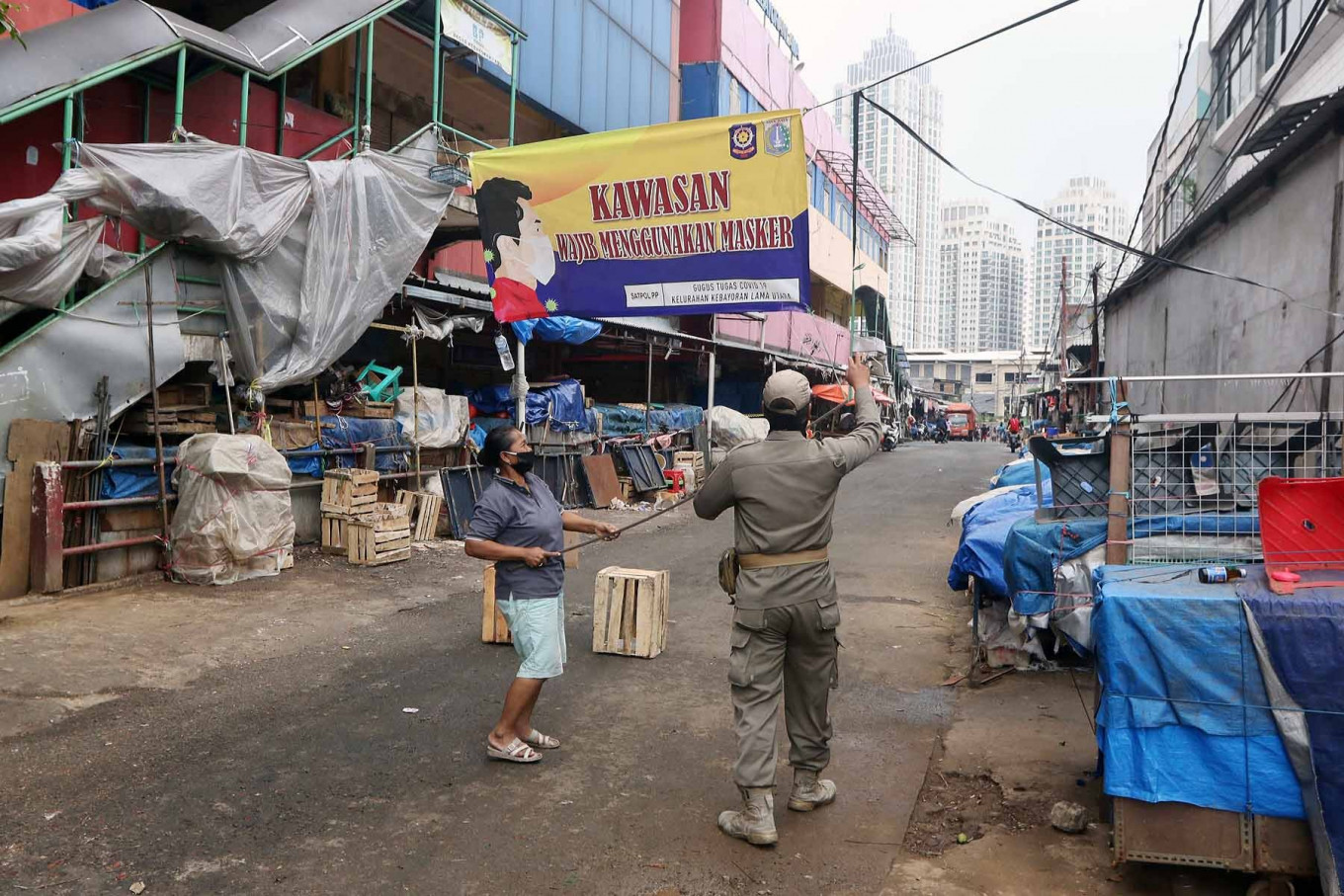 A Public Order Agency (Satpol PP) officer puts up a banner reminding residents that wearing masks in public is mandatory, at Kebayoran Lama Market in South Jakarta on June 19. The market was closed from June 18 to 20 after vendors tested positive for COVID-19. JP/Dhoni Setiawan
