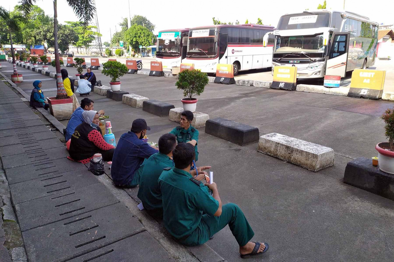 Intercity bus drivers and workers eat snacks while waiting for passengers at Kampung Rambutan terminal on Thursday. Bus service to West Java and Banten has resumed at the terminal. JP/P.J.Leo