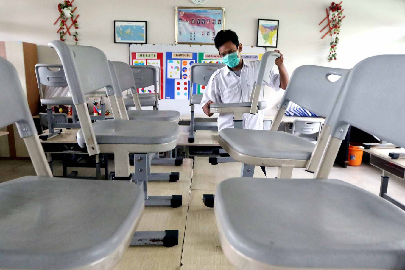 A school custodian arranges desks and chairs in a classroom at SD Bendungan Hilir 05 Pagi state elementary school in Central Jakarta on June 22. The classroom is cleaned twice a week to comply with COVID-19 health protocols. JP/Dhoni Setiawan