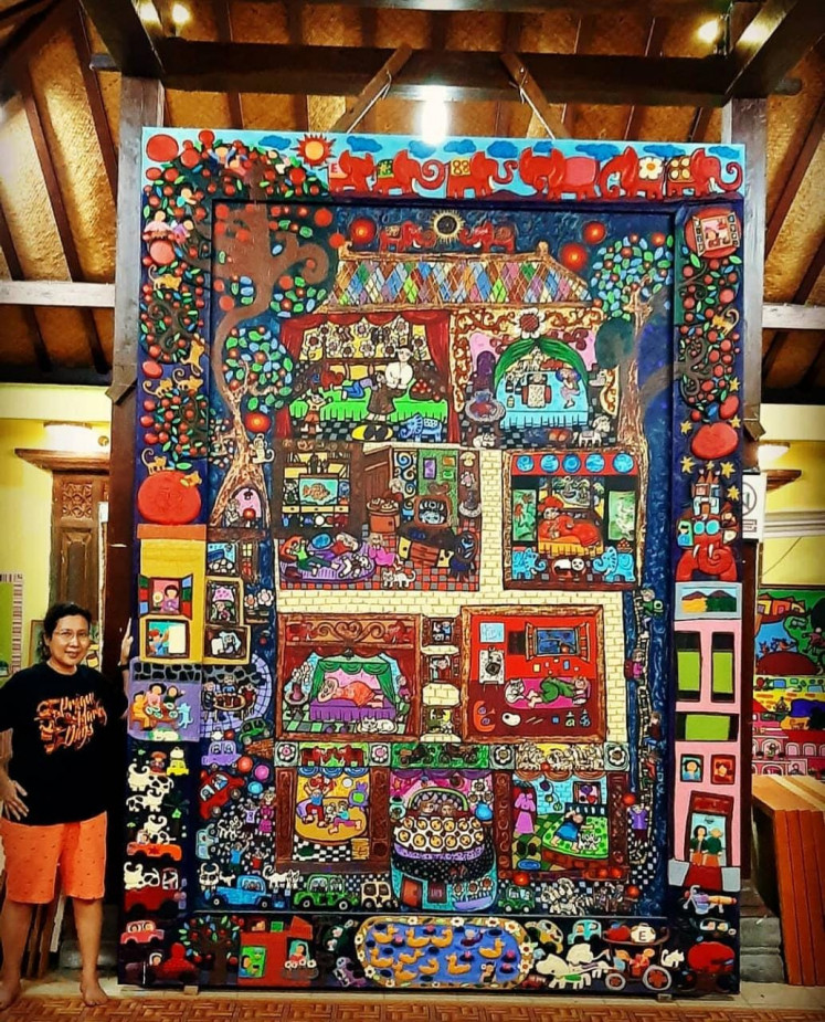 Go big: Erica Hestu Wahyuni poses with one of her painting that is three times her height.