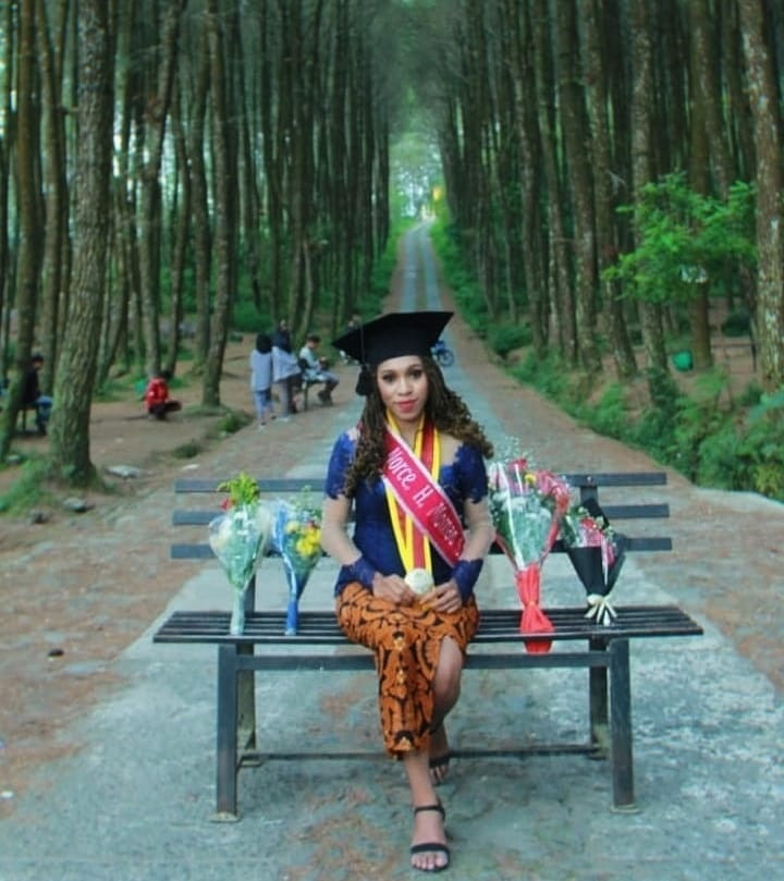 Norce Herlin Mak Momao poses for her graduation picture while surrounded by flowers from family and friends, after completing her master's degree in law from a university in Yogyakarta in May 2019. Norce is currently pursuing her doctoral degree and plans to return to her homeland in Sorong, Papua after she graduates.