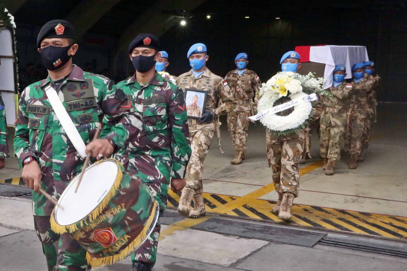 Soldiers carry the coffin and portrait of Sgt. Maj. Rama Wahyudi at Halim Perdanakusuma Air Force Base in East Jakarta on July 3. Rama died on June 22 after being shot during his peacekeeping mission with the United Nations Organization Stabilization Mission in the Democratic Republic of the Congo (MONUSCO). JP/Dhoni Setiawan