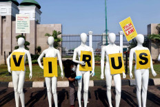 An environmentalist from Greenpeace Indonesia arranges mannequins as part of the NGO's protest in front of the House of Representatives' complex in Central Jakarta on June 29. Greenpeace urged lawmakers to stop deliberating problematic bills and focus on curbing COVID-19 in the country. The mannequins represented the dozens of other environmentalists who could not attend the protest because of large-scale social restrictions. JP/Dhoni Setiawan