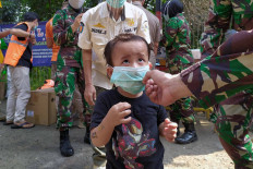 A soldier helps a boy put on a face mask during an event to mark the transitional period of large-scale social restrictions (PSBB) in East Jakarta on June 26. The boy was with his father (back, left), who was found violating PSBB measures and ordered to sweep the area as punishment. JP/P.J.Leo