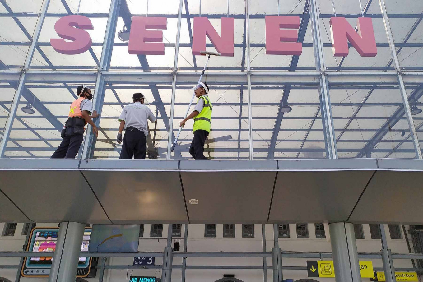 Workers clean the windows of Senen Station in Central Jakarta on June 29. State-owned train operator PT Kereta Api Indonesia (KAI) has resumed operations of several long-distance train services under strict health protocols. JP/P.J.Leo